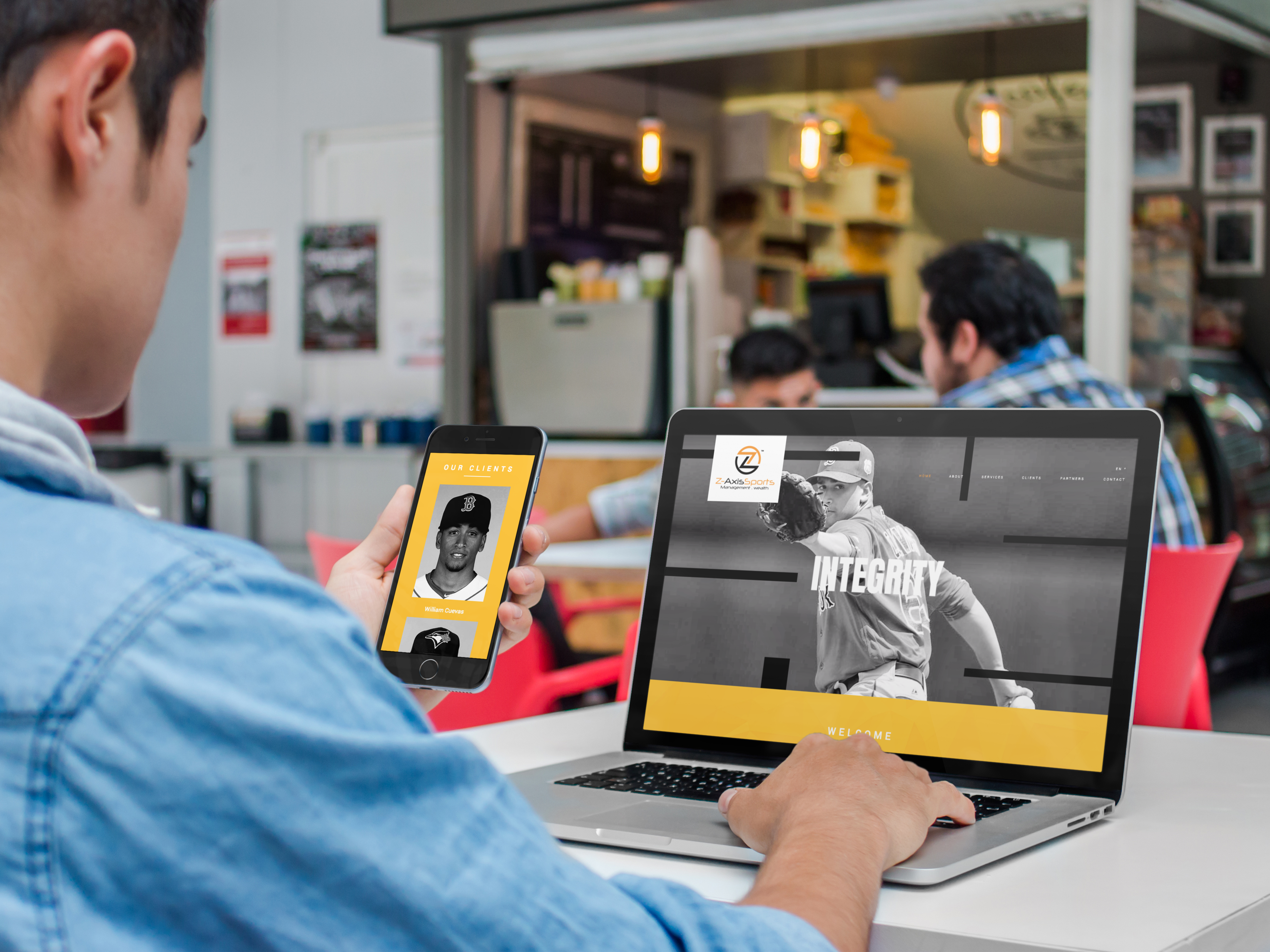 Left-Eye-Creations-iphone-and-macbook-mockup-of-a-young-man-at-the-cafeteria-a4635.png